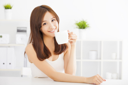 woman drinking tea: happy asian young drinking coffee Stock Photo