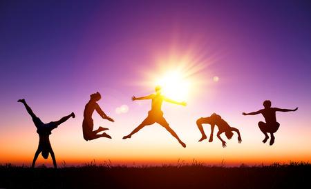 人: 快樂的年輕人在跳與陽光背景山