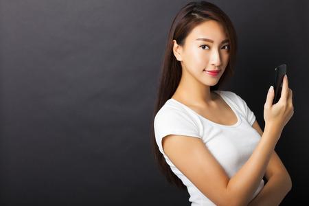 terra arrendada: jovem mulher segurando telefone inteligente com fundo preto Imagens