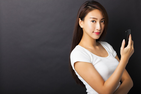 lady on phone: young woman holding smart phone with black background Stock Photo