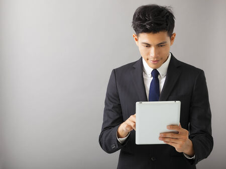 young smiling business man using tablet pc photo