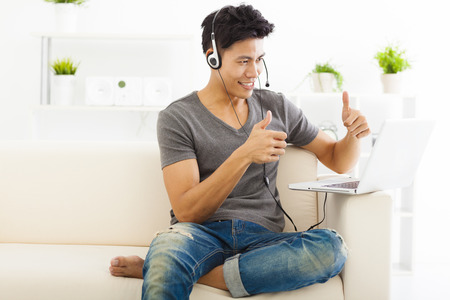 young Man sitting in sofa and using  laptop