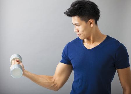 hombre: hombre fuerte y joven con mancuernas
