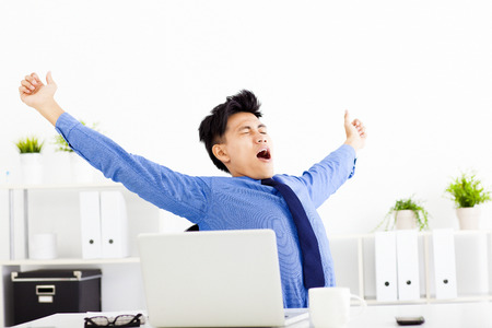 young businessman yawning at work in office photo