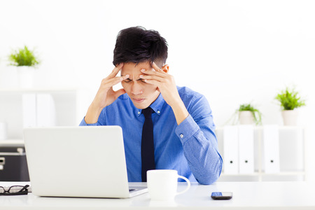 worried businessman: stressed businessman working in the office