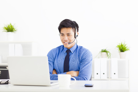 representatives: smiling businessman wearing a headset at the office