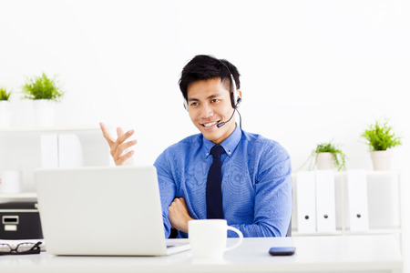 computer centre: sonriente hombre de negocios con un auricular en la oficina Foto de archivo