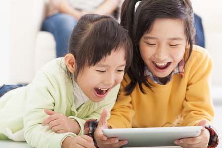 태블릿 컴퓨터를 사용하는 행복 아시아 어린 소녀