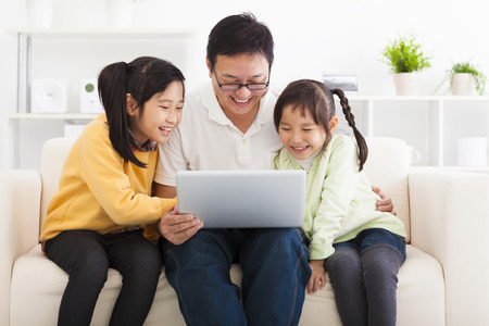 happy father using laptop with little girls photo