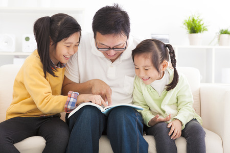 father read the book to children photo