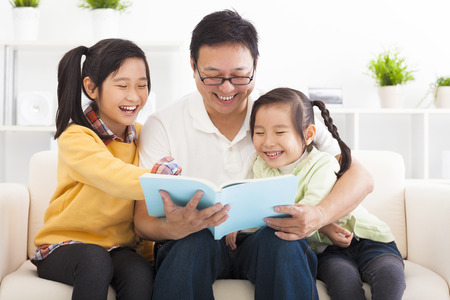 learning to read: happy father read the book to children