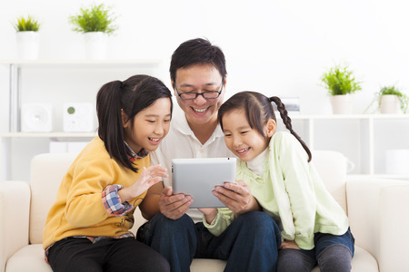 asian family fun: happy father using tablet pc with little girls Stock Photo