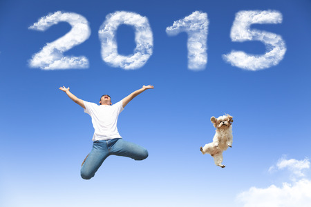 happy young people: happy new year 2015.young man and dog  jumping together with blue sky background Stock Photo