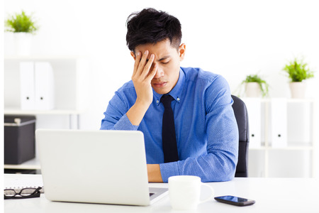 headache: stressed business man in the office Stock Photo