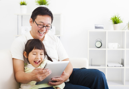 learning to read: happy father using tablet pc with little girl Stock Photo