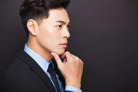 face side: side view Smiling businessman standing on black background Stock Photo