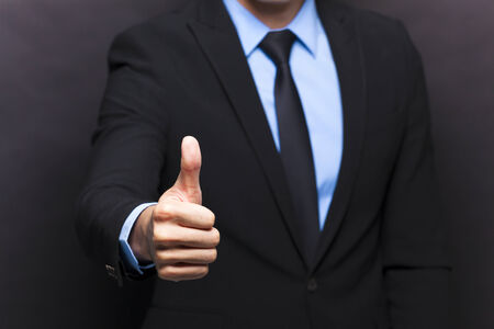 posing  agree: Businessman showing thumbs up sign