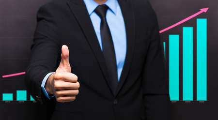 businessman with thumb up gesture and business growing graph concept photo