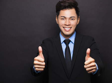 posing  agree: Smiling asian businessman with thumbs up Stock Photo