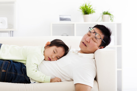 dad and child: father and daughter sleeping on the sofa