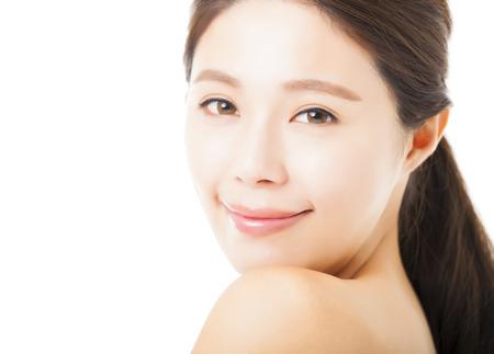 beauté: agrandi beau visage jeune femme isolé sur blanc