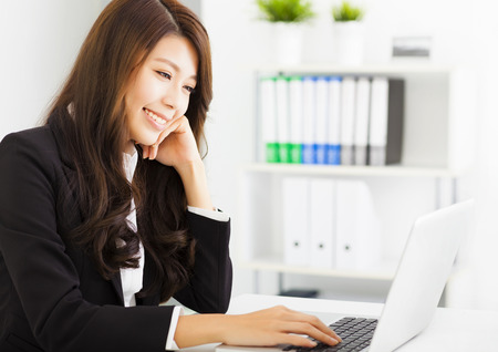 asian office lady: smiling young business woman working with  laptop Stock Photo