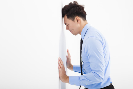 worried businessman: depressed young business man  leaning at the wall in office