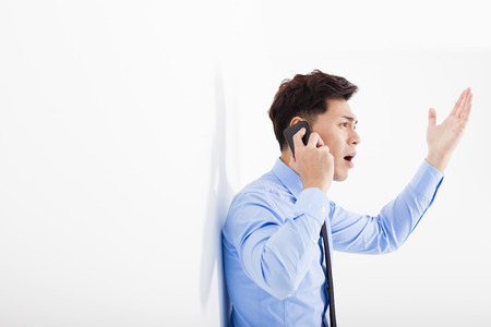 frustrated man: angry businessman talking on the phone in office Stock Photo