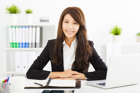 secretarias: Mujer de negocios joven que trabaja en la oficina sonriendo
