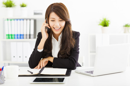asian office lady: happy business woman talking on the phone in office Stock Photo