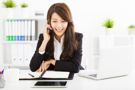 ejecutivo en oficina: Mujer de negocios feliz hablando por tel�fono en la oficina Foto de archivo