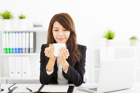 hot asian: Красивая молодая деловая женщина пить кофе в офисе Фото со стока