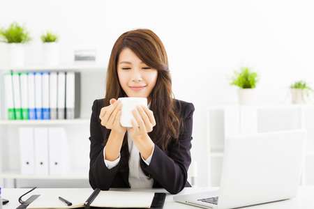asian office lady: beautiful young business woman drinking coffee in office