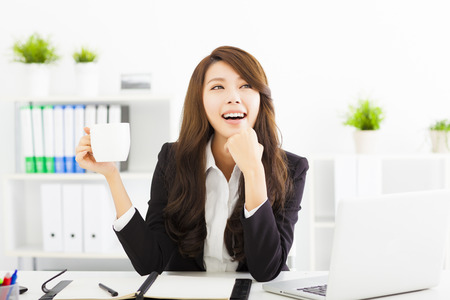 hot beverage: beautiful young business woman drinking coffee in office