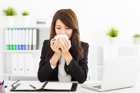 Красивая молодая деловая женщина пить кофе в офисе Фото со стока
