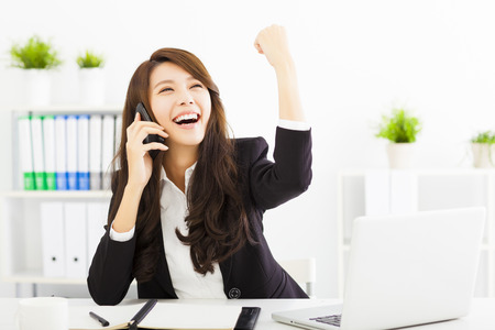 asia business: successful business woman talking on the phone in office