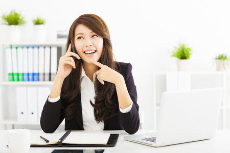 happy business woman talking on the phone in office photo
