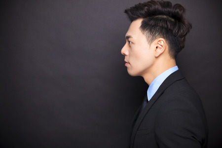 side view businessman standing before black background 스톡 콘텐츠