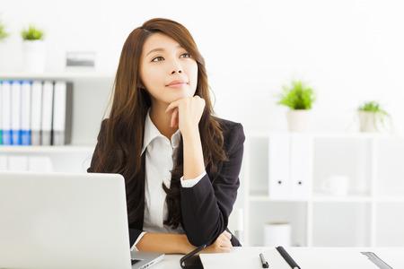 reflexionando: mujer de negocios joven pensando en la oficina sonriendo Foto de archivo