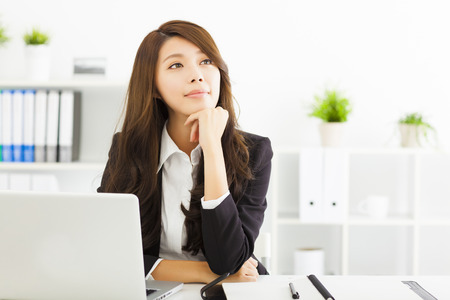 girl thinking: smiling young business woman thinking in the office Stock Photo