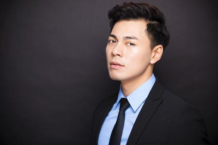 jonge zakenman staande voor een zwarte achtergrond Stockfoto