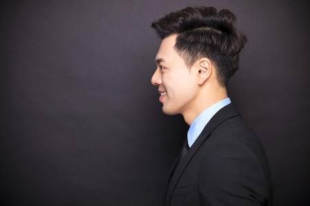 side view smiling businessman standing before black background