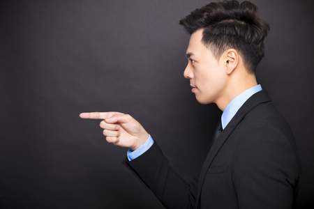 face side: side view angry businessman standing before black background