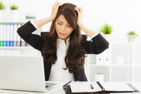 stressed  businesswoman sitting in office photo