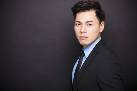 asia style: young businessman standing before black background Stock Photo
