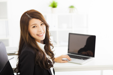 s úsměvem: šťastná mladá žena pracující v kanceláři