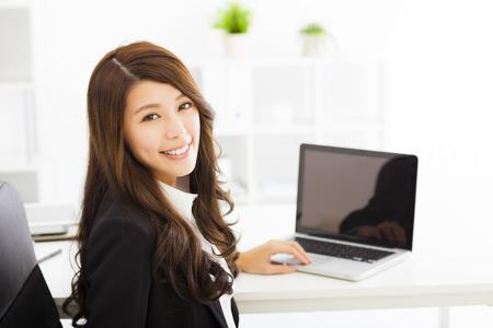 glückliche junge Geschäftsfrau, die im Büro