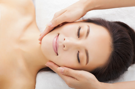 natural health: massage of face for woman in spa salon