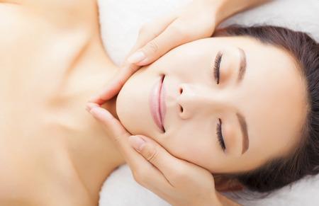 tratamientos corporales: el masaje de la cara de la mujer en el spa salón Foto de archivo