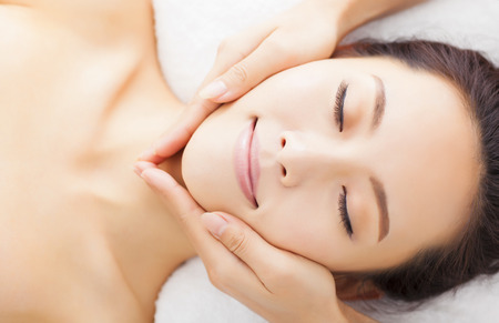 woman relaxing: massage of face for woman in spa salon